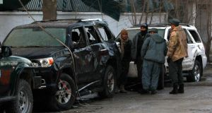 Afghan policemen inspect the wreckage of a vehicle outside a Lebanese restaurant . Photograph: Omar Sobhani/Reuters