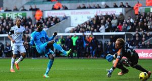 Emmanuel Adebayor rolls in his second and Tottenham's  third against Swansea City.Photograph:  Stu Forster/Getty Images