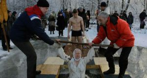 A Russian Orthodox Christian takes a dip in an icy pond during Orthodox Epiphany celebrations in the village of Strelna outside St Petersburg. Photograph: Reuters