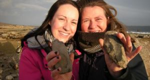 Lorna Moylan holding a polished stone axe and her aunt Elizabeth Moylan with a late Mesolithic mudstone axe which they  found at Ardmore, Connemara. Photograph: Kieran Moylan