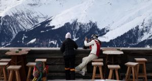 Skiers stop to look over the balcony and down to the town of Davos from the Chalet Gueggel restaurant on the Jakobshorn mountain in Davos, Switzerland. Photograph: Simon Dawson/Bloomberg