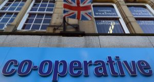 A logo sits on a sign outside a Co-Operative Bank Plc bank branch as a British union flag flies above in Keighley, UK. Photograph: Nigel Roddis/Bloomberg