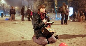 A protester prays as he holds an open Bible during an anti-government protest in  Kiev today. Photograph: EPA