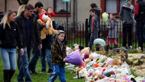 A boy lays flowers for  Mikaeel Kular in Edinburgh,Scotland. Photograph: Jeff J Mitchell/Getty Images