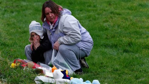 People look at floral tributes and soft toys left near the home of three-year-old Mikaeel Kular, in  Edinburgh, Scotland. Photograph: Russell Cheyne/Reuters