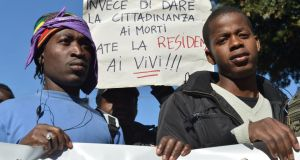 "Immigrants hold a placard reading ""Instead of giving citizenship to the dead, give it to the living!!"" on October 18th, 2013 in Rome during a demonstration. Photograph: ALberto Pizzoli/AFP/Getty Images"
