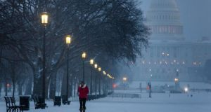 A visitor to the National Mall walks through a late afternoon snowfall in Washington yesterday. Photograph: EPA