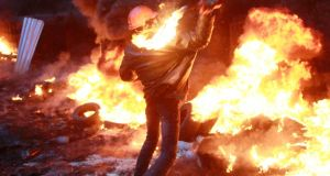 A pro-European protester throws a Molotov cocktail towards riot police near burning tyres during clashes in Kiev this evening. Photograph: Gleb Garanich/Reuters.