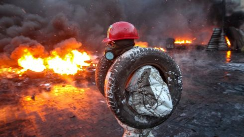 A pro-European integration protester carries tyres for burning at the site of clashes with riot police in Kiev. Photograph: Valentyn Ogirenko /Reuters