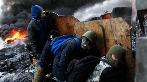 Pro-European integration protesters take cover behind makeshift shields at the site of clashes with riot police in Kiev. Photograph: David Mdzinarishvili /Reuters