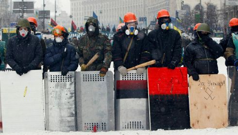 Pro-European protesters stand behind improvised shields during clashes with riot policemen in Kiev. Photograph: Gleb Garanich/Reuters