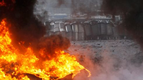 Riot police are seen through smoke from burning tyres during clashes with pro-European protesters in Kiev. Photograph: Gleb Garanich /Reuters