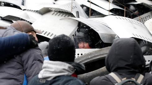 A riot police officer looks out as his colleagues take cover behind shields during clashes with pro-European protesters. Photograph: Vasily Fedosenko/Reuters