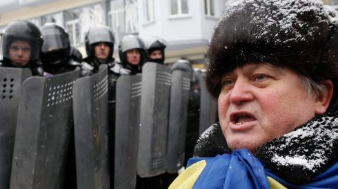 A demonstrator stands next to interior ministry members during a rally held by pro-European protesters in Kiev . Photograph: Vasily Fedosenko /Reuters