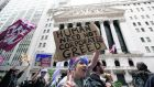 Protesters march in front of the New York Stock Exchange. Photograph: Brendan McDermid/Reuters