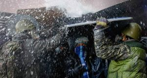 Pro-European integration protesters take cover from water sprayed from a fire engine at the site of clashes with riot police in Kiev January 23rd, 2014. Photograph: Vasily Fedosenko