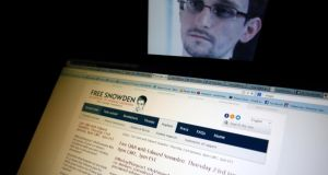 A portrait of former US spy agency contractor Edward Snowden is displayed behind a screen as he answers users' questions on Twitter.  Photograph: Dado Ruvic/Reuters