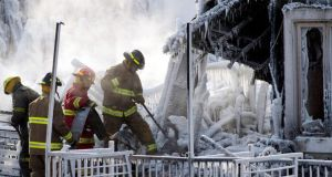 Firefighters search through the rubble after a fire destroyed a retirement home in Quebec, killing five people. Photograph: AP