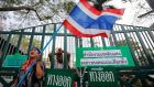 An anti-government protester waves a flag in front of the locked gates of a polling station her group had forced to close in Bangkok today. Photograph: Damir Sagolj/Reuters