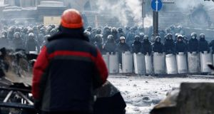 An anti-government protester looks at riot police standing behind their shields at the site of clashes in Kiev today. Photograph: Reuters