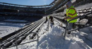 Workers attempt to clear a snow-covered MetLife Stadium in New Jersey last week. Photograph: New York Times