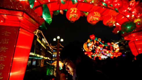 A man walks under the decorations at Yuyuan Garden, Shanghai. Photograph: Carlos Barria/Reuters