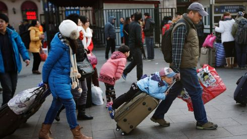A family carries their luggage while heading towards an entrance of the Beijing railway station. Photograph: Kim Kyung-Hoon/Reuters