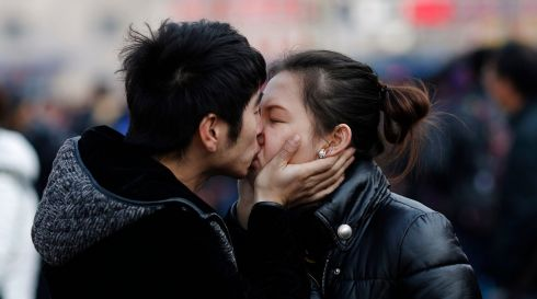 A couple kisses goodbye outside the Beijing railway station. Photograph: Kim Kyung-Hoon/Reuters