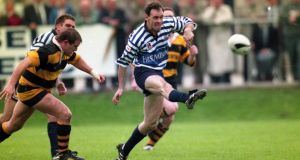 The worlds of Gaelic games and rugby collide as All-Ireland winning Meath footballer David Beggy avoids Young Munster's Peter Clohessy during a 1994 AIL game at Stradbrook. The two sports could feature at Stradbrook if the Cuala GAA club's purchase of part  of the rugby club's grounds goes ahead. Photograph: Inpho