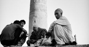 Drug addicts smoking heroin in the shadows of Herat's famous 15th century minarets.