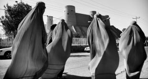 Women wearing traditional burghas walk past the ancient Citadel fortress in Herat. Photographs: John D McHugh
