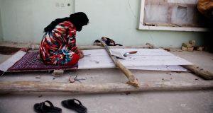 A woman weaves a carpet on a loom in her home in Mazar-e Sharif.