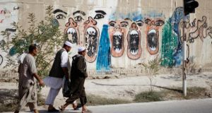 Men walk past graffitti that represents 'the suffering of women in Afghanistan'.