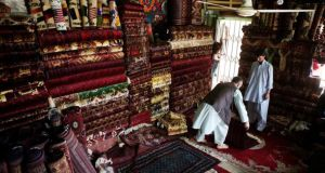 Carpet sellers examining their wares in mazar-e Sharif.