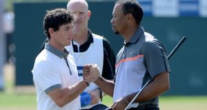 Rory McIlroy  and Tiger Woods  shake hands on the ninth green, their 18th hole, during the first round of the Omega Dubai Desert Classic on the Majlis course at the Emirates Golf Club in Dubai. Photograph: Ross Kinnaird/Getty Images
