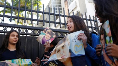 Fans of singer Justin Bieber hold up posters, in an alley behind the hotel where Bieber was presumed to be staying, in Miami Beach, Florida January 24, 2014. Three Florida police officers were suspended for giving Bieber an unauthorised escort from a Miami area airport, a couple of days before his arrest for drunk driving after he was caught drag racing on Miami Beach.     Photograph: Andrew Innerarity/Reuters