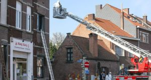 Police investigators and  firefighters inspect the scene of a fire in which two Irish students died in Leuven this morning. Photograph: EPA