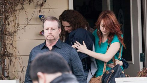 An unidentified person covered under clothing leaves the Seattle, Washington home of the parents of Amanda Knox, surrounded by others including her father, Curt Knox, the day before the January 2014 verdict in Florence.  Photograph: David Ryder/Getty Images