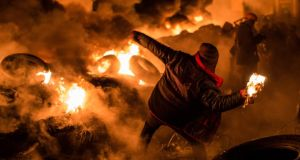 An anti-government protester throws a Molotov cocktail during clashes with police in Kiev. Photograph: Brendan Hoffman/Getty Images