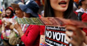 "Anti-government protesters hold ""No Vote"" stickers and Thai baht banknotes to donate to their leader during a march through Chinatown in Bangkok today. Photograph: Damir Sagolj/Reuters"