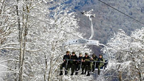 Members of Russian security forces ride in a chairlift above the men's Olympic downhill course at the Rosa Khutor alpine resort. Photograph: Kai Pfaffenbach/Reuters