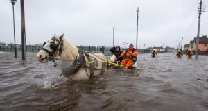 Local man Ger Hogan and his horse ferry people in and out of Saint Mary's Park in Limerick today after the River Shannon burst its banks in Limerick City. Photograph: Sean Curtin