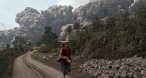 A villager runs as Mount Sinabung erupts at Sigarang-Garang village in Karo district, Indonesia's North Sumatra province today. Photograph: Reuters