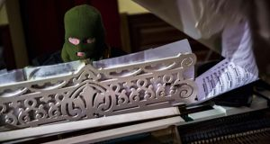 A masked man plays the grand piano to an audience of anti-government protesters in  Kiev City Hall, occupied by opposition forces, yesterday. Photograph: Thomas Peter/Reuters