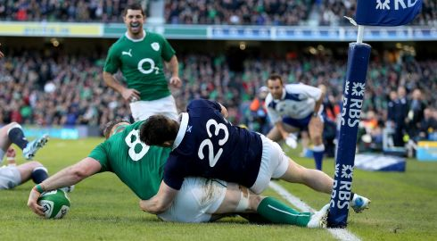 Jamie Heaslip gets tackled into touch by Max Evans of Scotland just before the line. Photograph: Dan Sheridan/Inpho