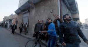 Residents react during what activists said was an air raid by forces loyal to Syrian president Bashar Al-Assad on Aleppo over the weekend. Photograph: Reuters/Saad Abobrahim
