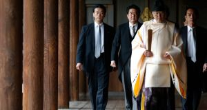 Japan's prime minister Shinzo Abe (second from left) is led by a Shinto priest as he visits Yasukuni Shrine in Tokyo on December 26th, 2013. Photograph: Toru Hanai/Reuters