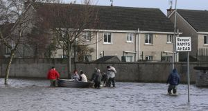 Residents use a boat to navigate flood waters after a flash flood on the Lee Estate in Limerick City. Photograph: Niall Carson/PA Wire