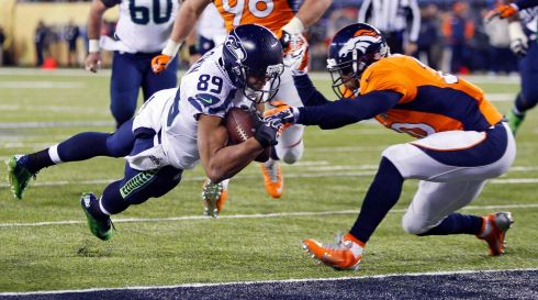 Back to the game. Seattle Seahawks wide receiver Doug Baldwin (89) dives into the end zone for a touchdown past Denver Broncos free safety Mike Adams during the fourth quarter. Photograph: Carlo Allegri/Reuters