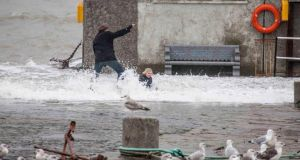 A man and a child feel the force of a wave on the pier at Bullock Harbour, Co Dublin, yesterday.   Photograph: Aidan Tarbett/Provision